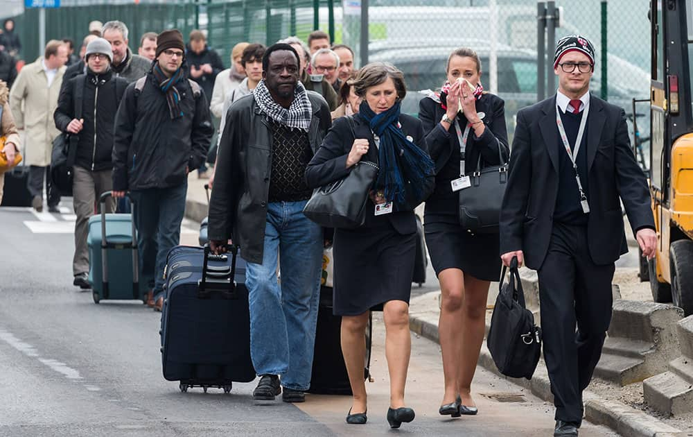 People react as they walk away from Brussels airport after explosions rocked the facility in Brussels, Belgium.