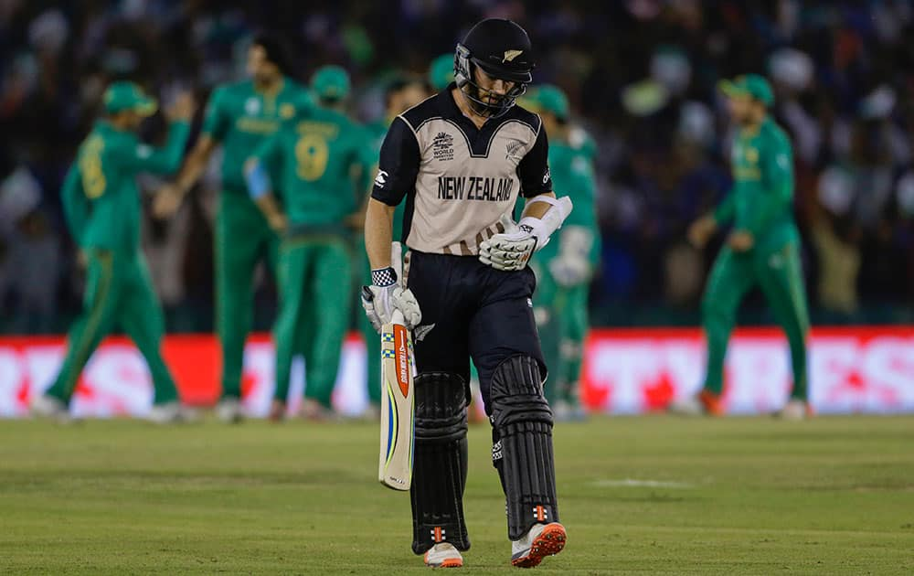 New Zealand's Kane Williamson walks back after his dismissal as Pakistan players celebrate during their ICC World Twenty20 2016 cricket match in Mohali.