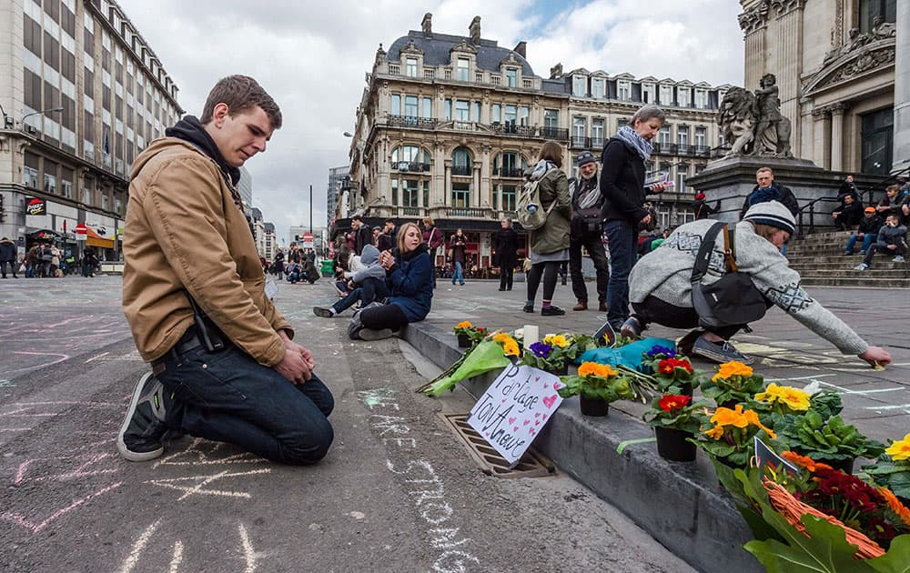 A man looks at flowers and messages outside the stock exchange in Brussels.