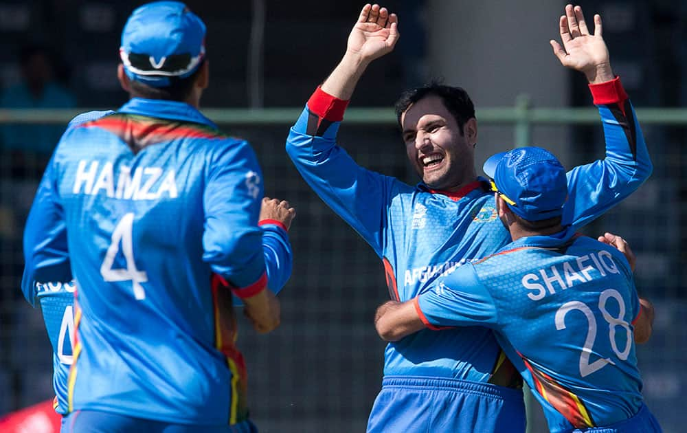 Afghanistan's Mohammad Nabi celebrates with team mates after claiming the wicket of England's Joe Root during their ICC Twenty20 2016 Cricket World Cup match at the Feroz Shah Kotla cricket stadium in New Delhi.