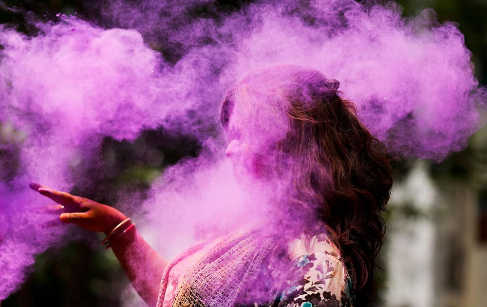 A Bangladeshi woman shuts her eyes as colored powder is smeared on her face during celebrations marking Holi, the Hindu festival of colors, in Dhaka, Bangladesh.