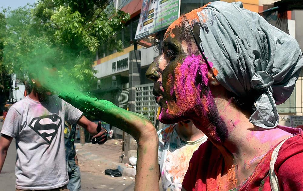 A Foreign tourist sprays colour while celebrating Holi in Kolkata.