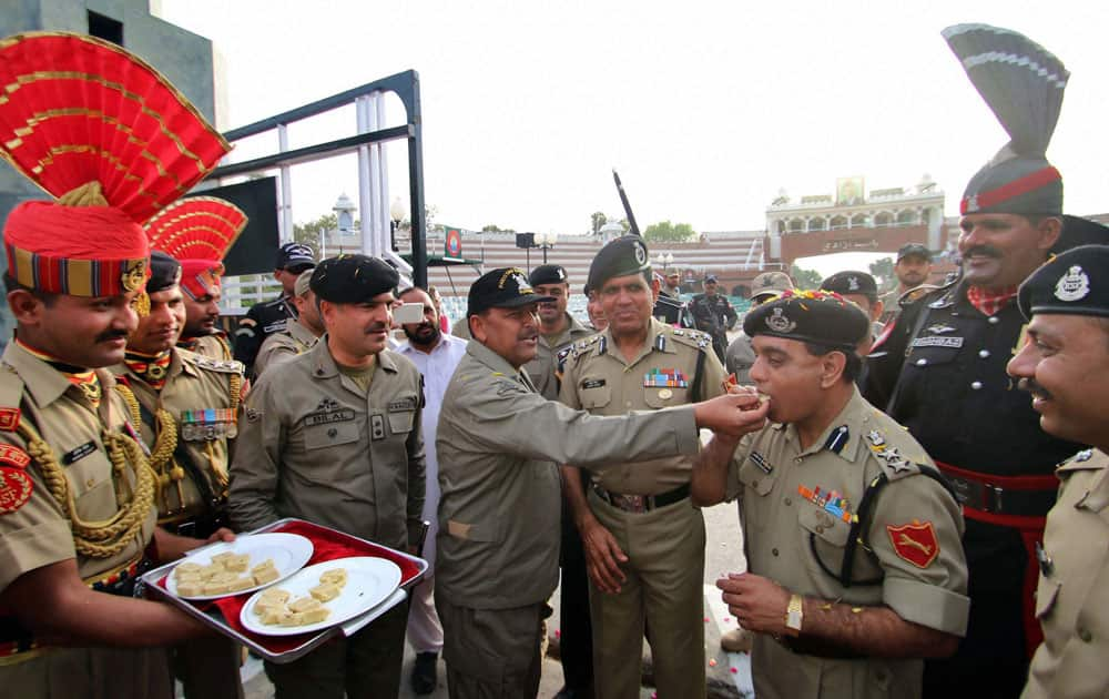 Pak Rangers offer sweets to BSF officials at Zero line during celebration of Holi with flowers petals with their counterparts of Pak Rangers at Attari international border.