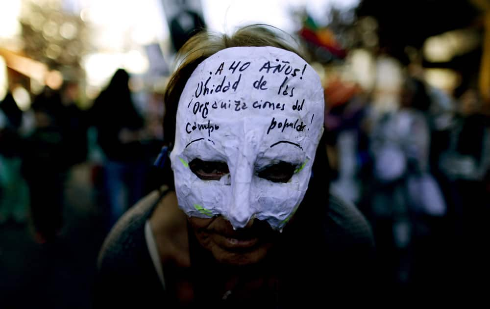 A demonstrator wears a mask that reads in Spanish: