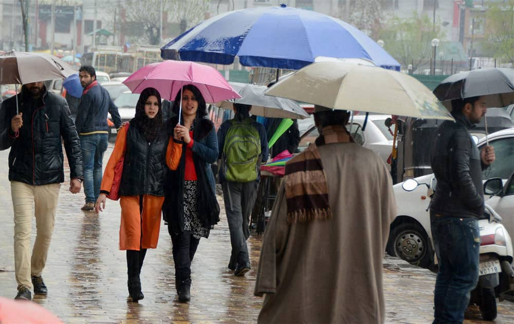 People walk under umberallas to protect themselves during incessant rains at Lal Chowk in Srinagar.