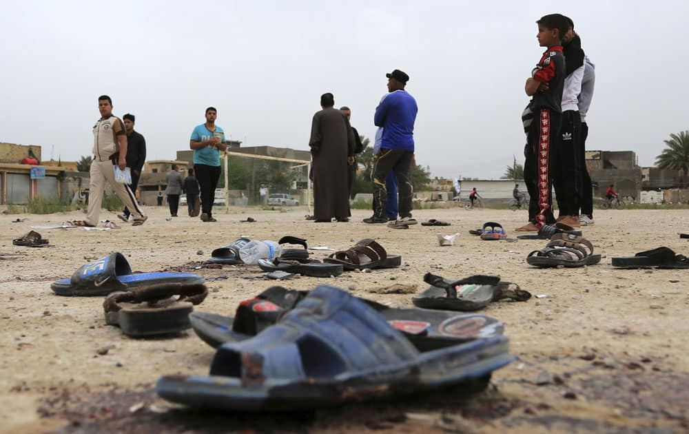 People inspect the aftermath of a suicide bombing at a soccer field in Iskandariya, 25 miles (about 40 kilometers) south of Baghdad, Iraq.