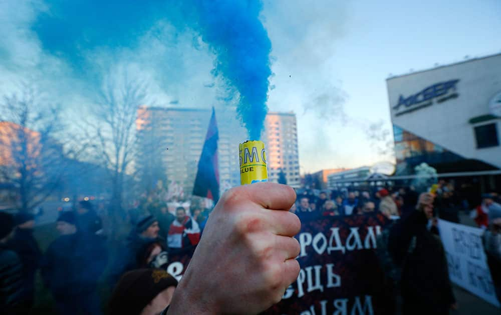 A Belarusian opposition protester holds a lighted flare during a rally in Minsk, Belarus.