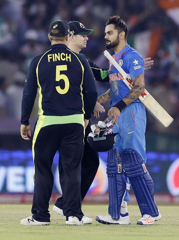 India's Virat Kohli, right, is congratulated by Australian player's Steve Smith and Aaron Finch after winning their ICC World Twenty20 2016 cricket match by six wickets in Mohali.