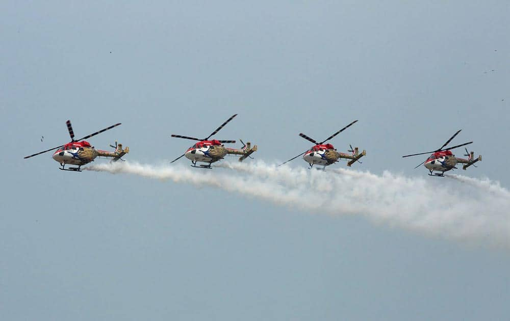 Sarang helicopters maneuvering their skill at the inauguration of 9th edition of Defexpo-16 in Panaji, Goa.