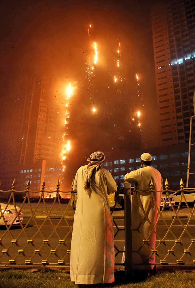 Two Emirati officials as a fire spreads up the side of the watch a high-rise building in Ajman, United Arab Emirates.