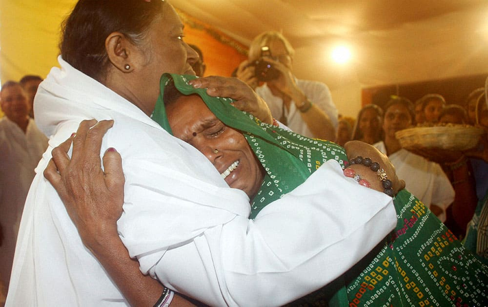 Spiritual leader, Mata Amritanandamayi, hugs a devotee during a function in Ahmadabad.