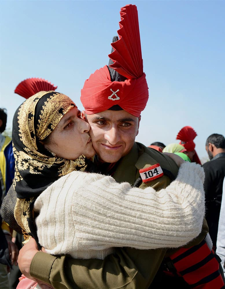 A woman embraces her son during the pipping ceremony after Passing Out parade at JKLIRC Army Headquaters in Srinagar on Tuesday. As many as 145 Kashmiri youth formally joined Army after Attestation cum Passing out Parade.
