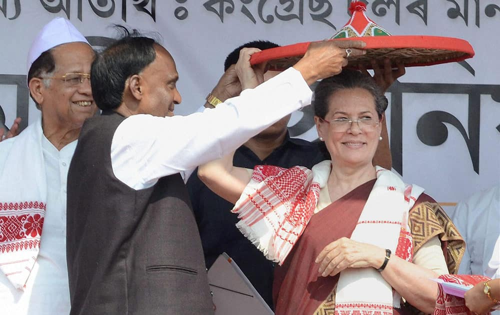 Congress president Sonia Gandhi being felicitated with a traditional Assamese japi (hat), gamocha and sarai by Congress candidate from Biswanath Assembly constituency Nurjamal Sarkar while Assam Chief Minister Tarun Gogoi (L) looks on at an election rally at Biswanath Chariali in Sonitpur district, Assam.
