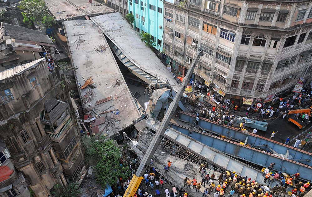 Locals and rescue workers clear the rubbles of a partially collapsed overpass in Kolkata.