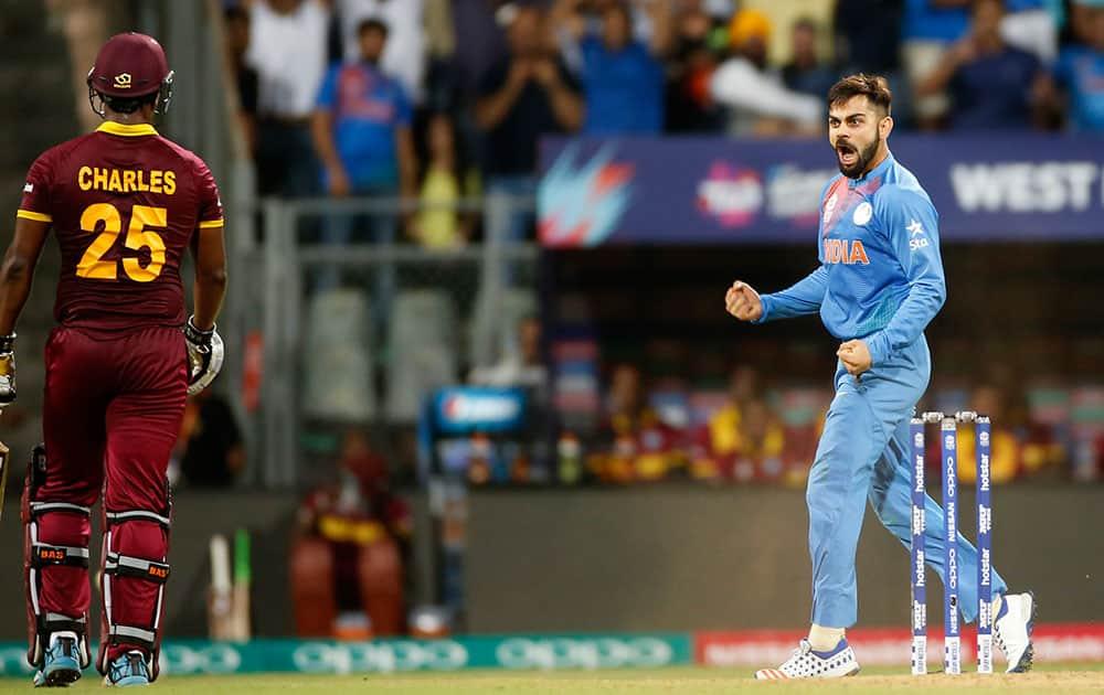 Virat Kohli celebrates after taking the wicket of West Indies Johnson Charles, left, during their ICC World Twenty20 2016 cricket semifinal match at the Wankhede stadium in Mumbai.