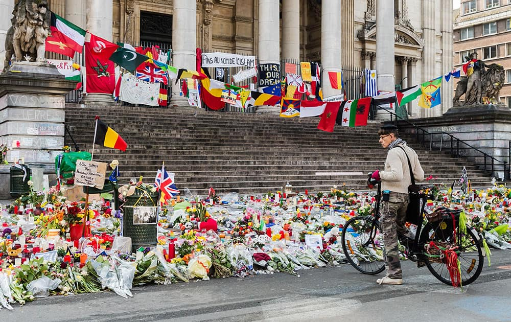 A man looks at a memorial site for the victims of the Brussels attacks at the Place de la Bourse in Brussels, Belgium.