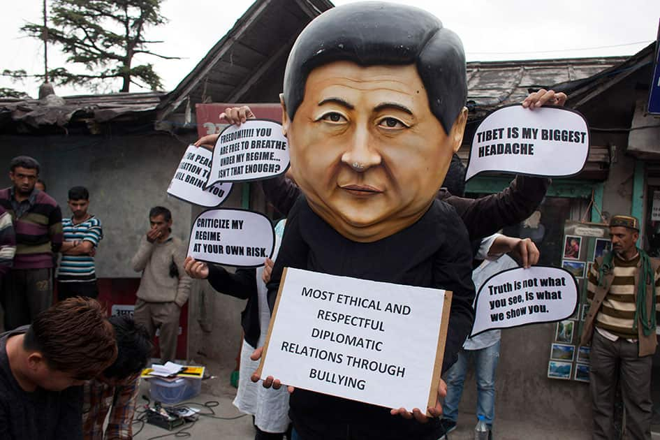 A Tibetan activist wears a mask in the likeness of the Chinese president Xi Jinxing during a street protest in Dharmsala.
