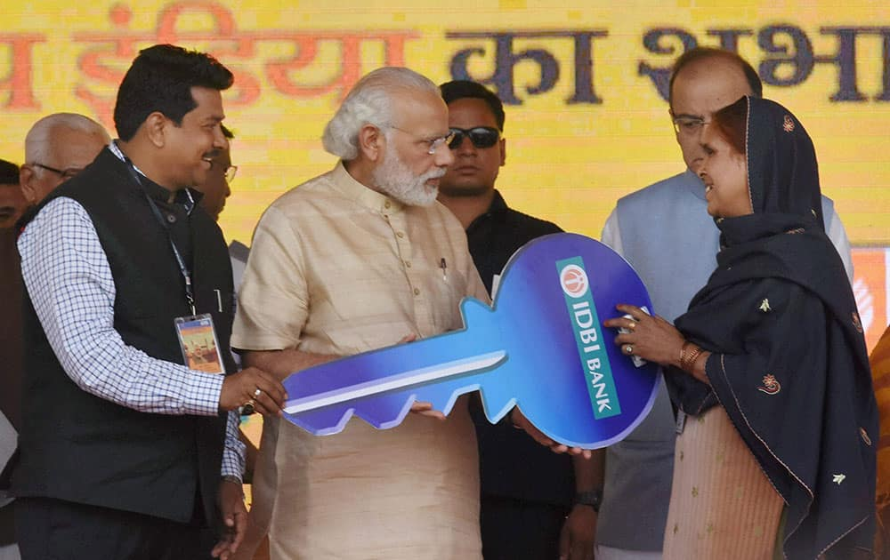 Prime Minister Narendra Modi hands over keys of an e-rickshaw to a beneficiary under Pradhan Mantri Mudra Yojana launched under Stand up India Scheme in Noida.
