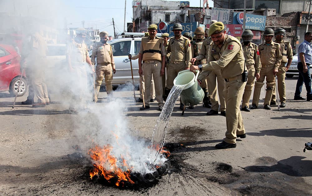 Policemen clear a road block during students protest against police action on students of the National Institute of Technology (NIT) in Srinagar.