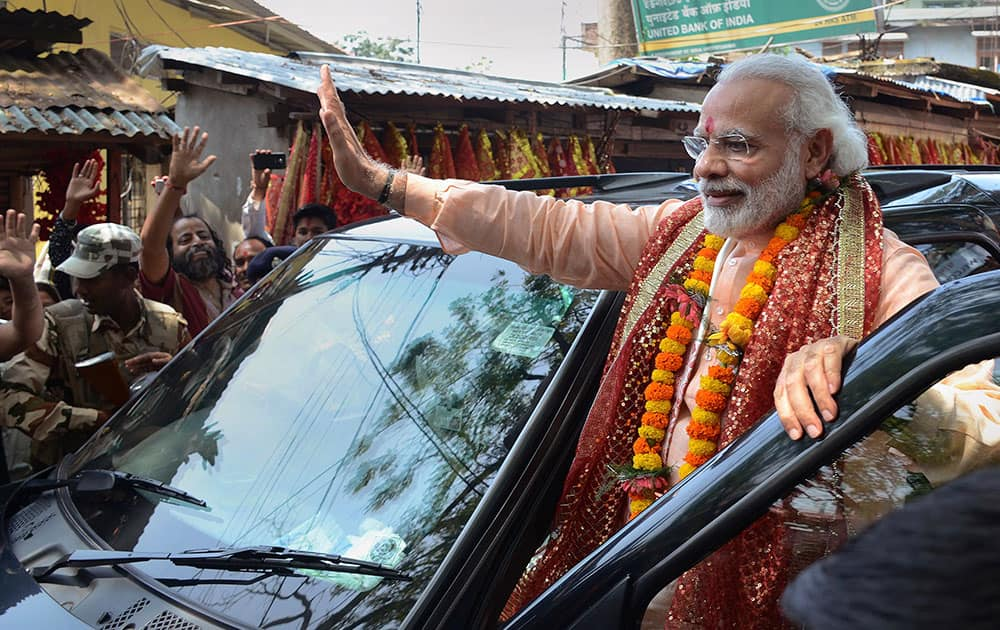 Prime Minister Narendra Modi waves to his supporters as he leaves after offering prayers the Kamakhya temple in Guwahati.