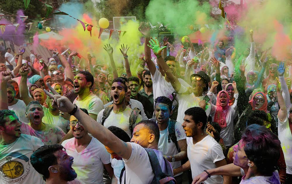 Egyptians toss colored powder into the air during the Festival of Colors organized by the Indian Cultural Center in Cairo, Egypt.