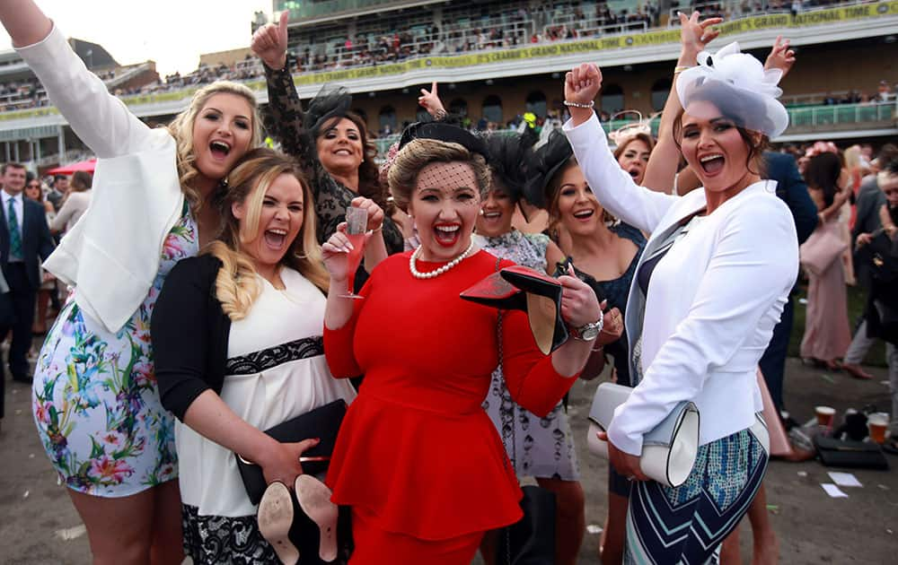 Racegoers pose for a photograph during Ladies Day of the Grand National Festival at Aintree Racecourse, Liverpool, England.