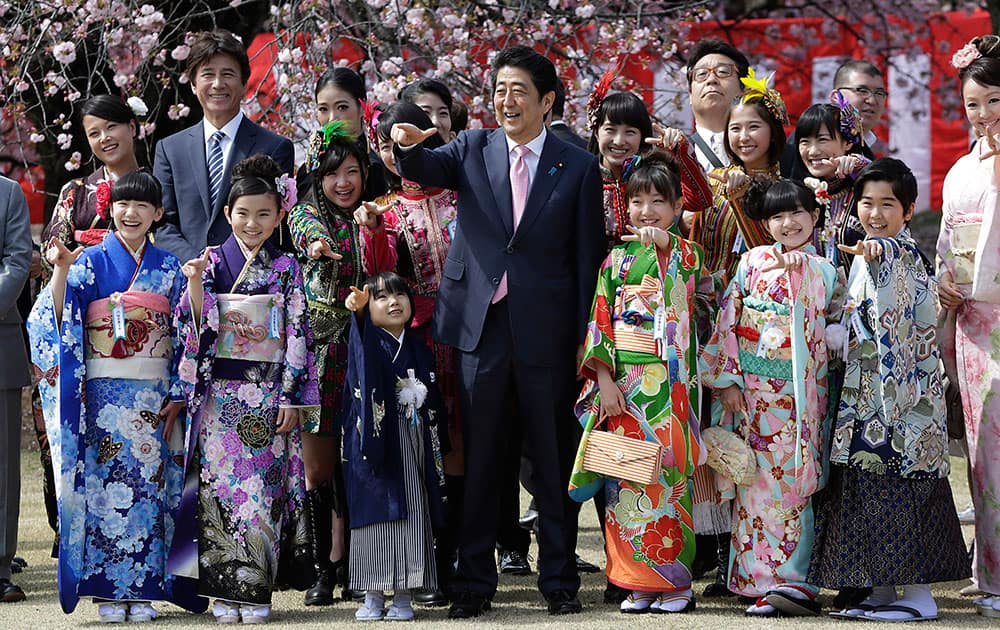 Japanese Prime Minister Shinzo Abe, center, poses for a group photo with members of Japanese pop group Momoriro Clover Z and Japanese child actors wearing Japanese kimono during a cherry blossom viewing party hosted by Abe at Shinjuku Gyoen National Garden in Tokyo.