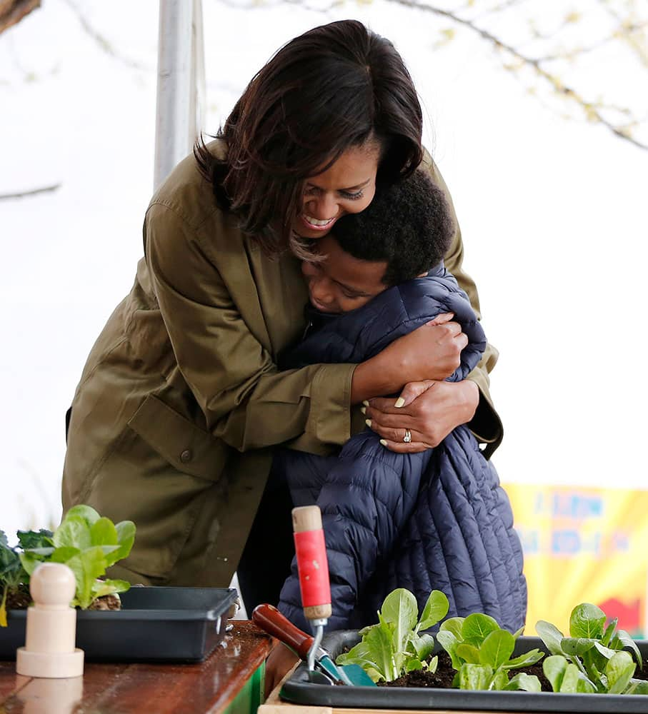 Firs lady Michelle Obama gives a hug to fifth grade student Peter Barkely during a visit to Philip's Academy Charter School as part of her American Garden Tour.