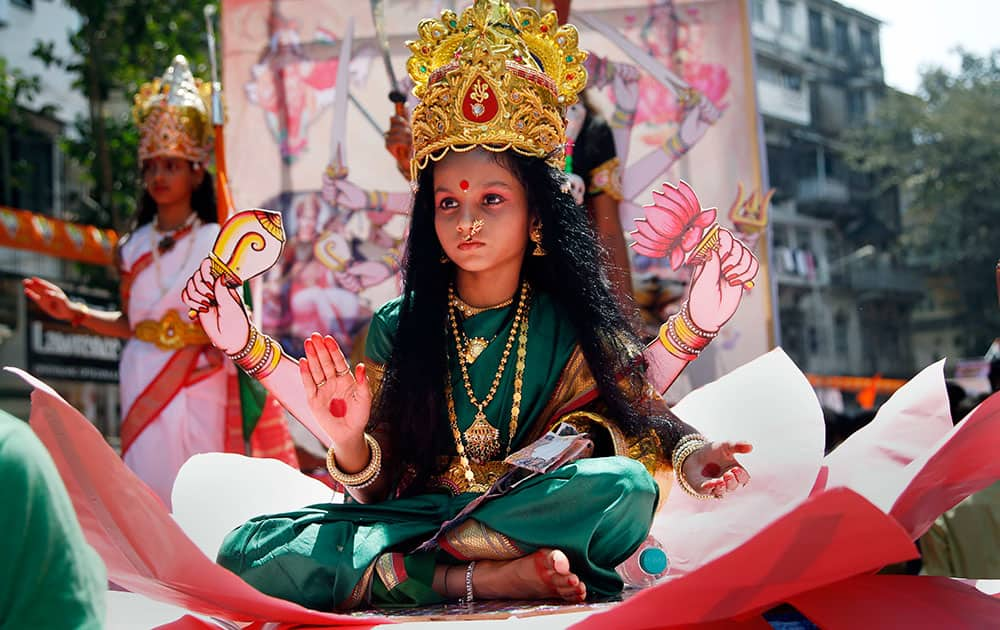 A young Indian girl dressed as Hindu goddess Laxmi participates in a procession to mark