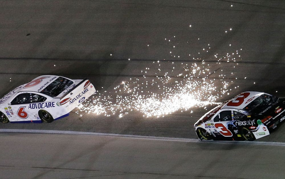 Trevor Bayne's car, left, showers sparks in front of Austin Dillon during the NASCAR Sprint Cup Series auto race at Texas Motor Speedway in Fort Worth, Texas.