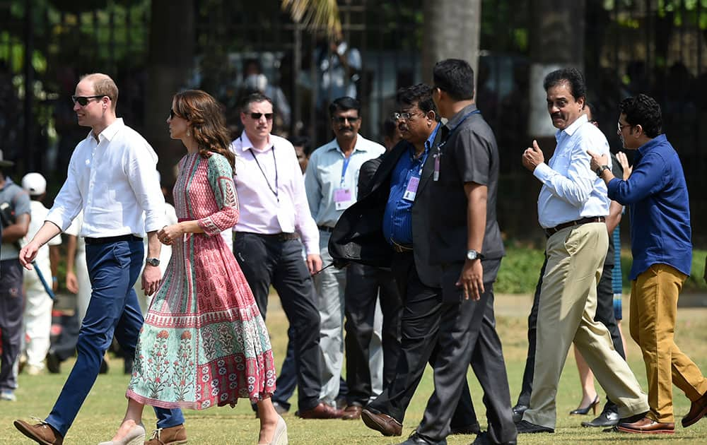 The Duke and Duchess of Cambridge, Prince William, left and his wife, the former Kate Middleton, walk with officials as former Indian cricketers Sachin Tendulkar, right and Dilip Vengsarkar, second right, speak during a charity event at the Oval Maidan in Mumbai, India.