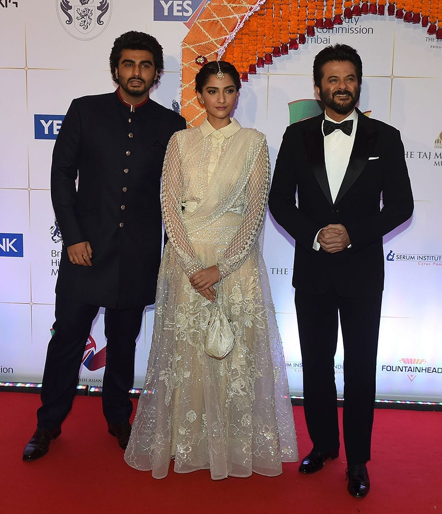 Bollywood actress Sonam Kapoor, center, actors Anil Kapoor, right and Arjun Kapoor pose for photographers after arriving for a charity ball at the Taj Mahal Palace hotel attended by the Duke of Cambridge, Prince William, and his wife, Kate, the Duchess of Cambridge, in Mumbai.