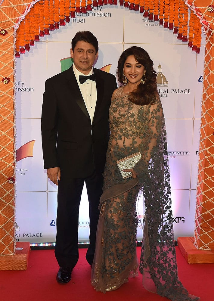 Bollywood actress Madhuri Dixit, right and husband Shriram Nene pose for photographers after arriving for a charity ball at the Taj Mahal Palace hotel attended by the Duke of Cambridge, Prince William, and his wife, Kate, the Duchess of Cambridge, in Mumbai.