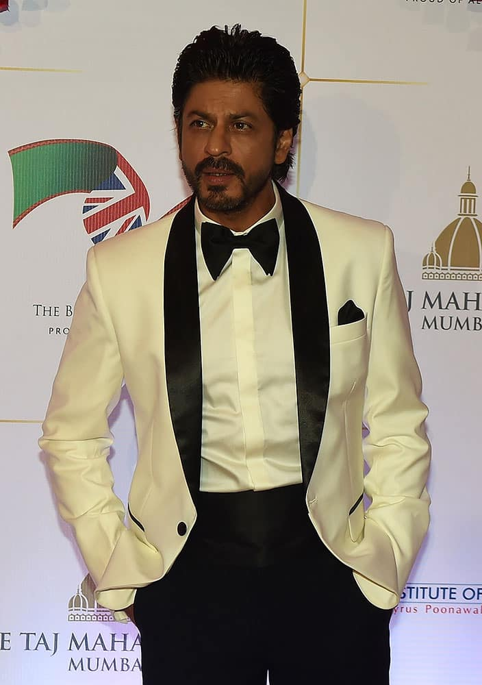 BOLLYWOOD ACTOR SHAH RUKH KHAN POSES FOR PHOTOGRAPHERS AFTER ARRIVING FOR A CHARITY BALL AT THE TAJ MAHAL PALACE HOTEL ATTENDED BY THE DUKE OF CAMBRIDGE, PRINCE WILLIAM, AND HIS WIFE, KATE, THE DUCHESS OF CAMBRIDGE, IN MUMBAI.
