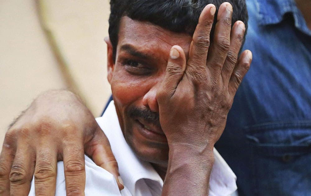 An unidentified man weeps as bodies of victims lie outside a morgue at the Kollam district hospital after a massive fire broke out during a fireworks display at the Puttingal temple complex in Paravoor village, Kollam district, southern Kerala.