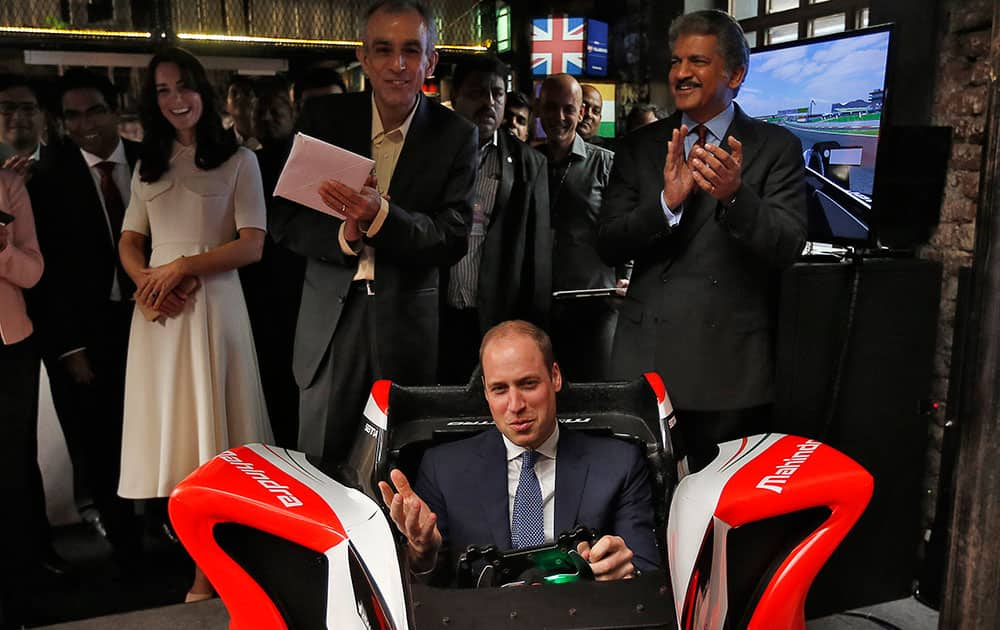Britain's Prince William steers a Formula E simulator at an event on young entrepreneurs in Mumbai.