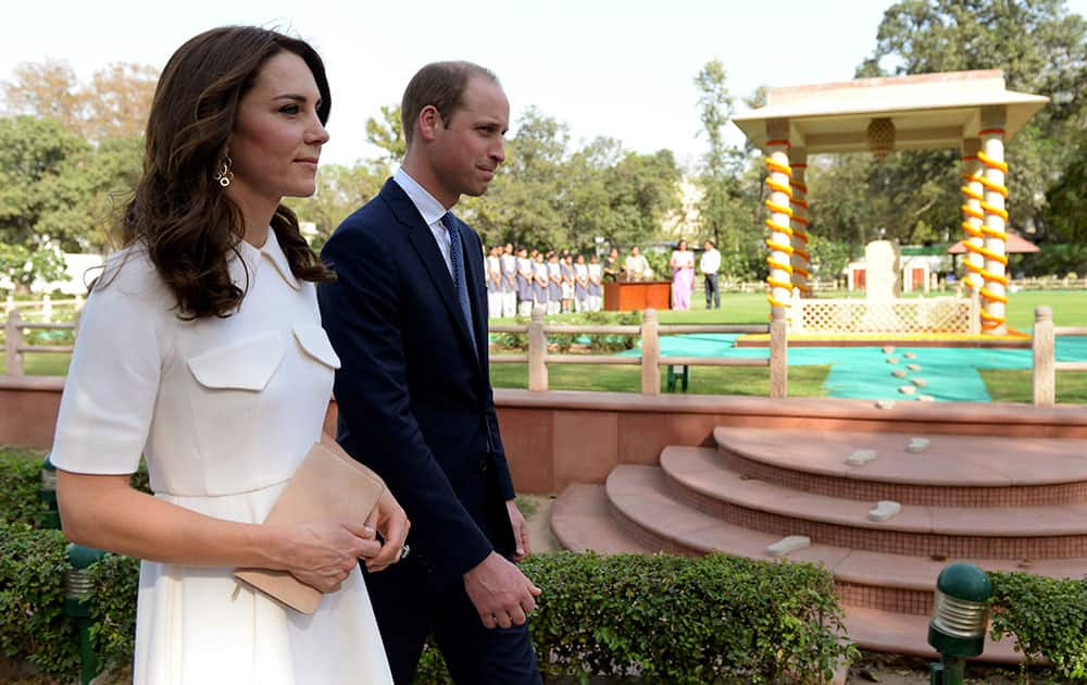 Britain's Prince William, right, the Duke of Cambridge, and his wife Kate, the Duchess of Cambridge, walk together as they pay tribute during a visit to Gandhi Smriti, an Indian museum dedicated to Mahatma Gandhi in New Delhi.