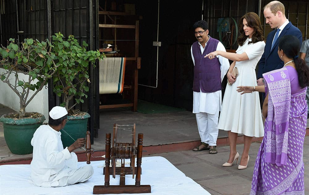 Britains Prince William along with his wife Kate Middleton, the Duchess of Cambridge having a close view of spinning of thread on a Charkha (spinning wheel) during a visit to Gandhi Smriti in New Delhi.