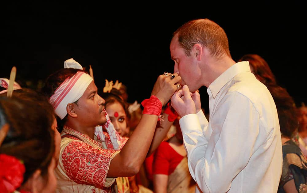 An Assamese traditional Bihu dancer explains to Britain's Prince William, right, how to play a traditional instrument made of bamboo in Diphlu River Lodge in the Kaziranga National Park, east of Gauhati, northeastern Assam state.