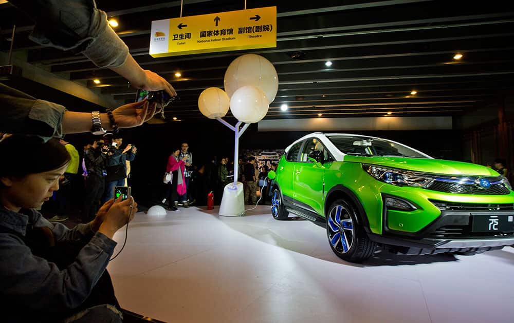 visitors examine the Yuan, BYD's latest Plug-in Hybrid mini SUV introduced at the BYD Dreams Conference in Beijing, China.