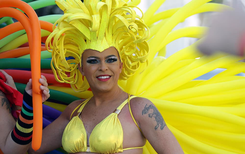 Christian Torrealba wears a costume made of balloons while waiting for the start of a parade along Ocean Drive at Miami Beach Gay Pride, in Miami Beach, Fla.