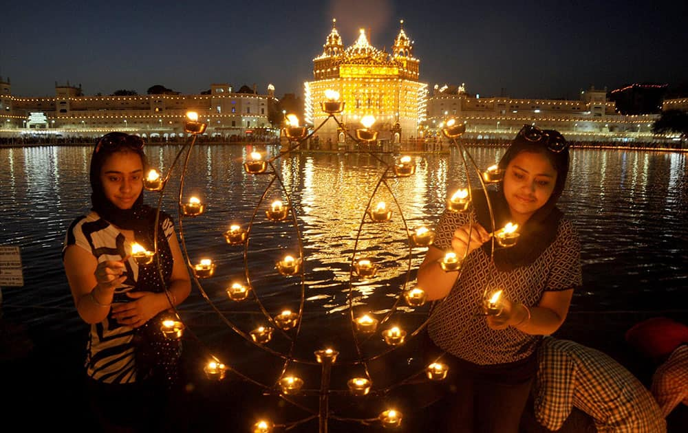 "Devotees lights up candles at the illuminated Golden Temple on the occasion of ""Baisakhi"" festival at Amritsar."