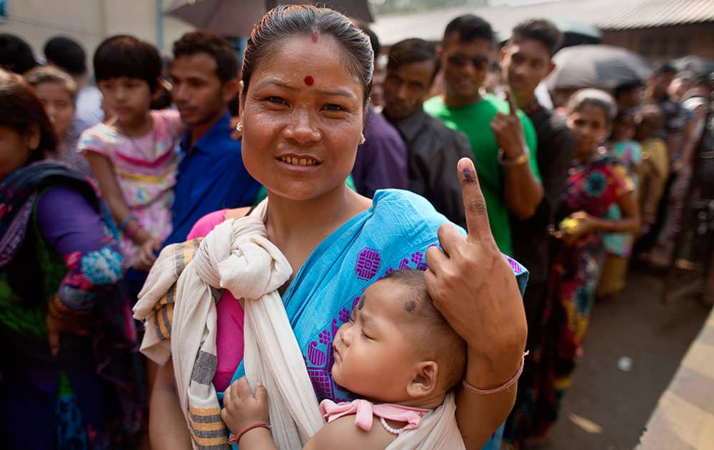 A woman carrying her child shows her ink marked finger after casting her vote during the second phase of Assam state assembly elections outside a polling station on the outskirts of Guwahati, Assam.