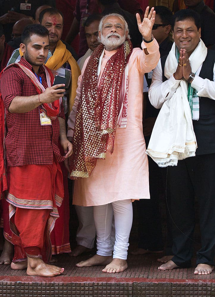 Prime Minister Narendra Modi waves to his support after offering prayers at a holy pond inside the Kamakhya temple in Guwahati. Modi is on an election campaign tour for the second and final phase of state Assembly elections.