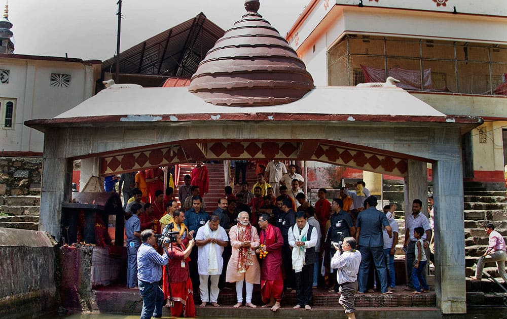 Prime Minister Narendra Modi offers prayers at a holy pond inside the Kamakhya temple in Guwahati. Modi is on an election campaign tour for the second and final phase of state Assembly elections.