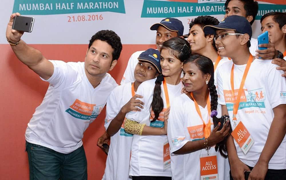 Cricket legend Sachin Tendulkar takes selfie with the children during announcement of IDBI Federal Life Insurance Mumbai Half Marathon in Mumbai.