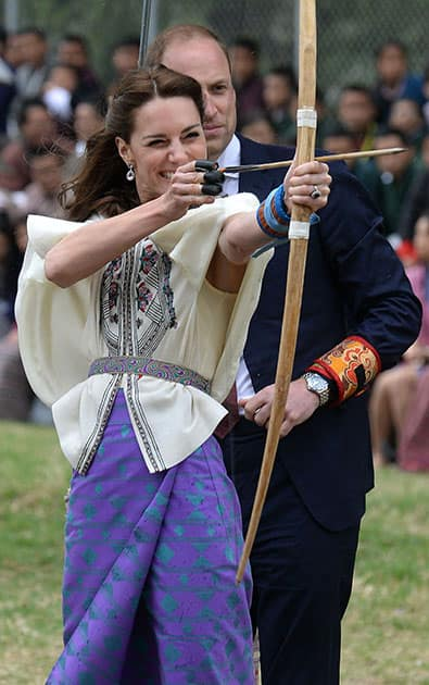 Kate Duchess of Cambridge takes part in an archery event as her husband Prince William looks over her shoulder in Thimphu, Bhutan, during day five of the royal tour to India and Bhutan.