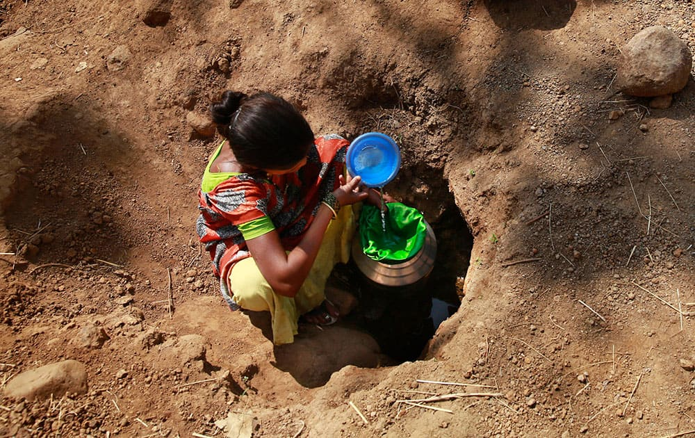 A woman collects water from a spring at Raichi Wadi village, 120 kilometers (75 miles) north-east of Mumbai. Decades of groundwater abuse, populist water policies and poor monsoons have turned vast swaths of central and western India into a dust bowl, driving distressed farmers to suicide or menial day labor in the cities.