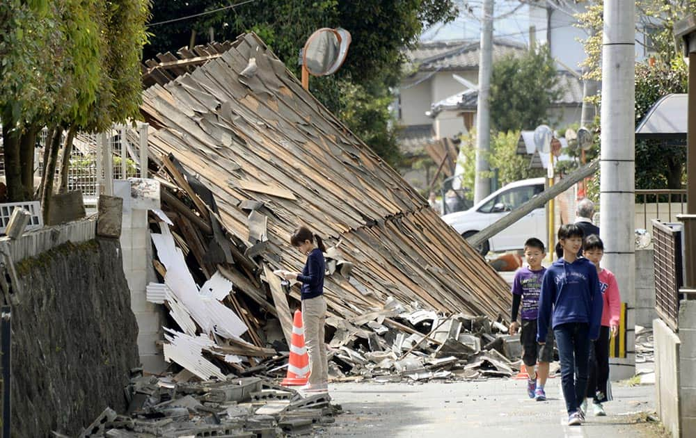 Children walk past a house collapsed by a magnitude-6.5 earthquake in Mashiki, Kumamoto prefecture, southern Japan.