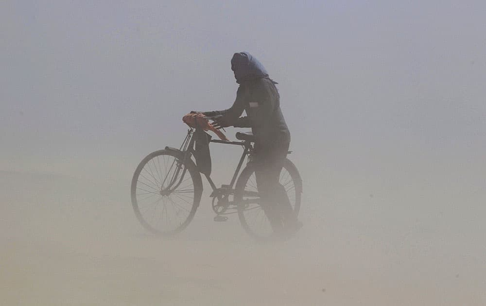 A cyclist cover himselves as he walk on the river bank of Ganga during a dust storm in Allahabad.